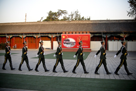 Changing of the Guard ceremony in front of a poster about the Guards.