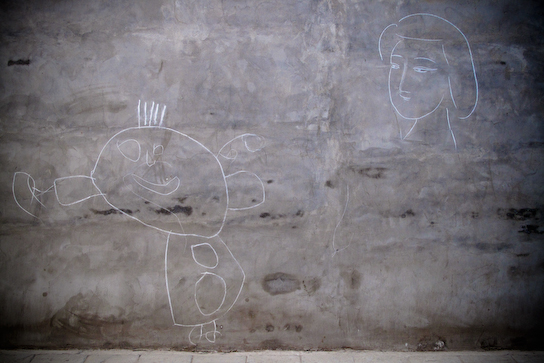 Kid's drawings on the side of a wall.