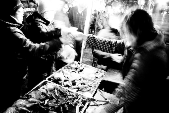 A vendor selling chicken's feet and heads.