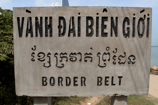 Border sign in Vietnamese, Khmer, English.